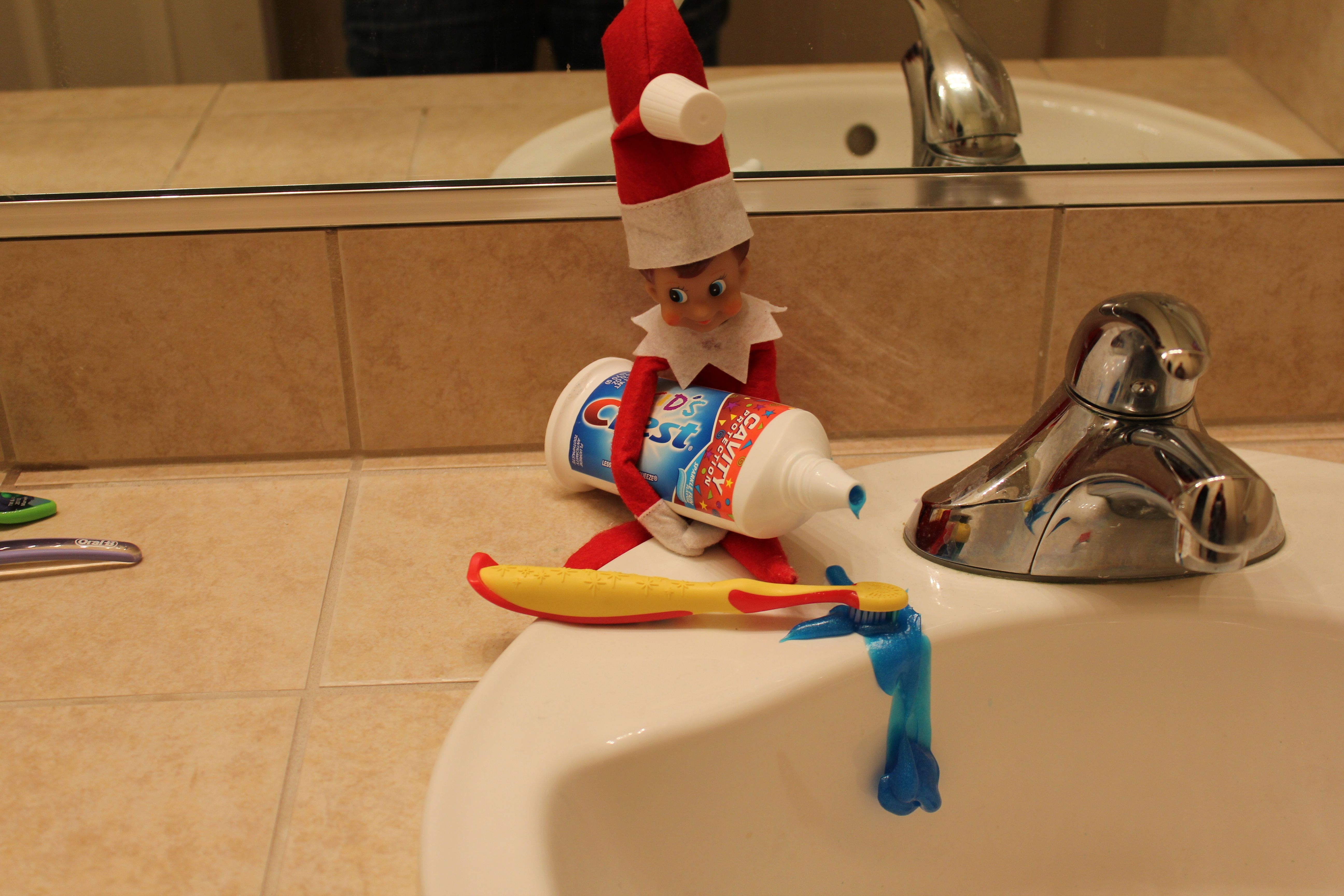 elf trying to put toothpaste on toothbrush