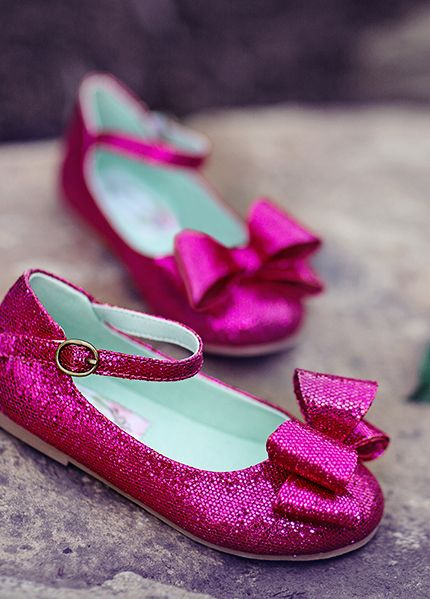 Miriam in Raspberry - Made of luminous, iridescent glitter, these double bow maryjanes are super sparkly!  We find this style exceptionally versatile and perfect paired with party dresses and every-day-wear alike.  Lined in textured satin.  They include a matching clip!