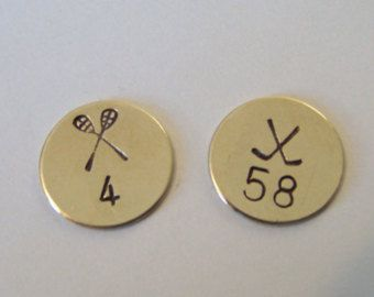 Custom Stamped Lacrosse and Hockey Floating Disks, available in gold or silver and can customize with team numbers
