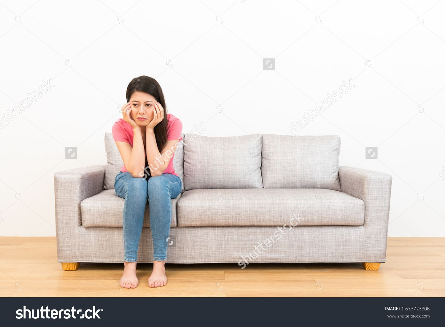 sad woman sitting on couch and weeping crying thinking of. Black Bedroom Furniture Sets. Home Design Ideas