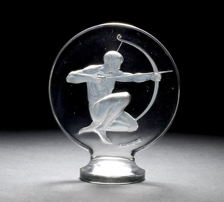 An 'Archer' glass mascot, by Rene Lalique, French, introduced 3rd August 1926, moulded 'R Lalique' to lower edge, in clear glass featuring deep impressed moulded depiction of a kneeling archer, 12cm high, two minor internal bubbles to base.