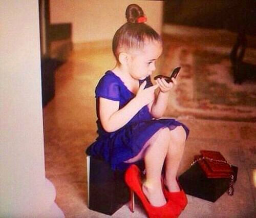 Little Girl wearing red high heel Shoes