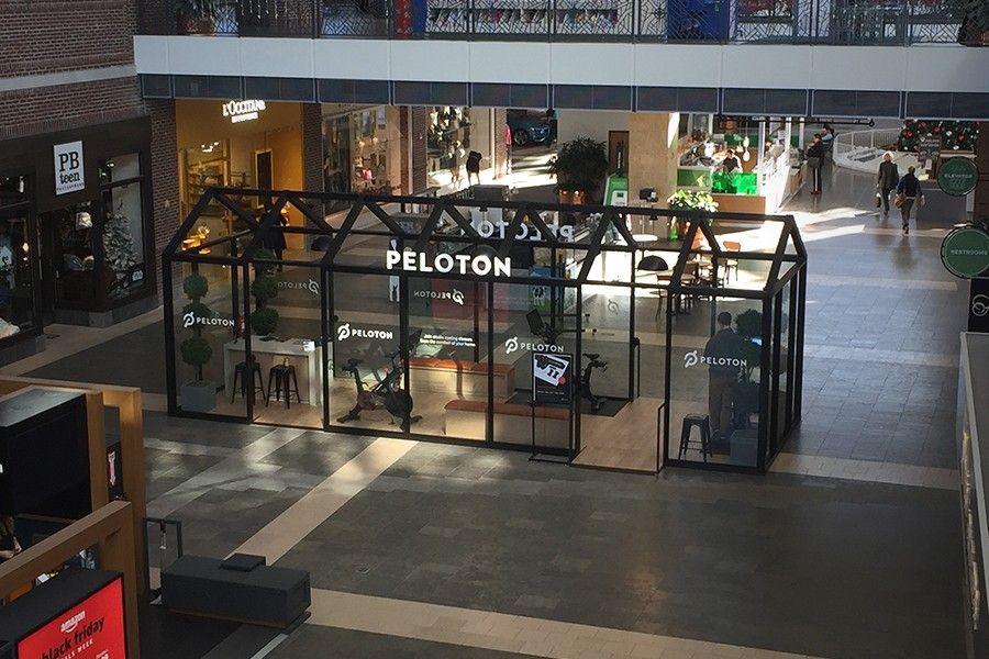 At A Ggp Property A Peloton Kiosk Sits In A Main Area The Kiosk Is A Large Black Iron Frame Surrounding Glass Panes Filled Wi Mall Kiosk Kiosk Design Kiosk