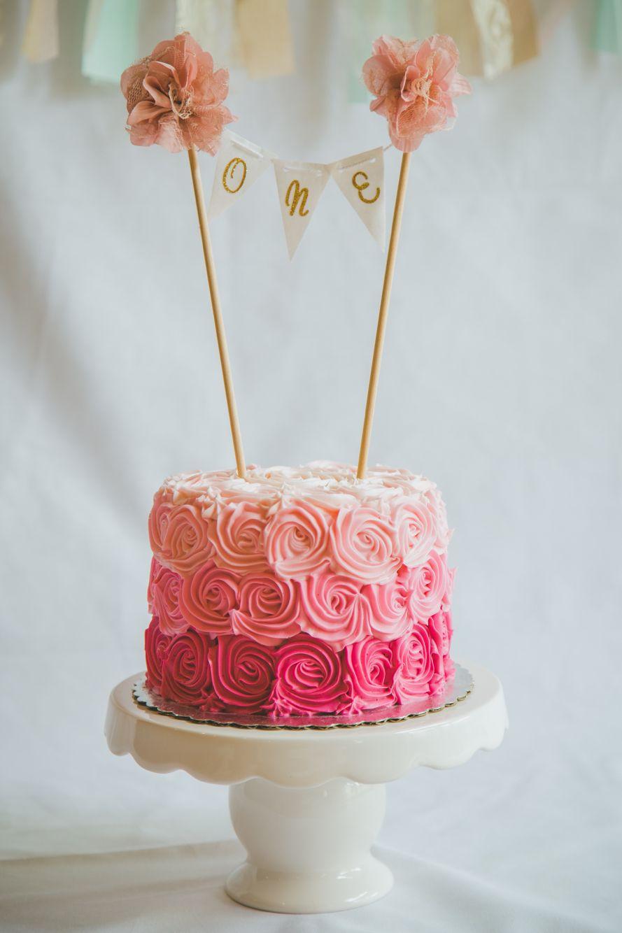Pastel flores tonos de rosas, banderines dorados con pompones