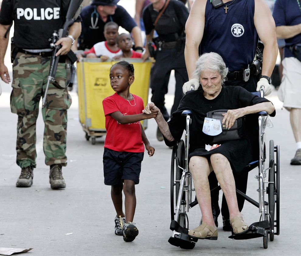 Tanisha Blevin, 5, holds the hand of fellow Hurricane Katrina victim Nita LaGarde, 105, as they are evacuated from the convention center in New Orleans.