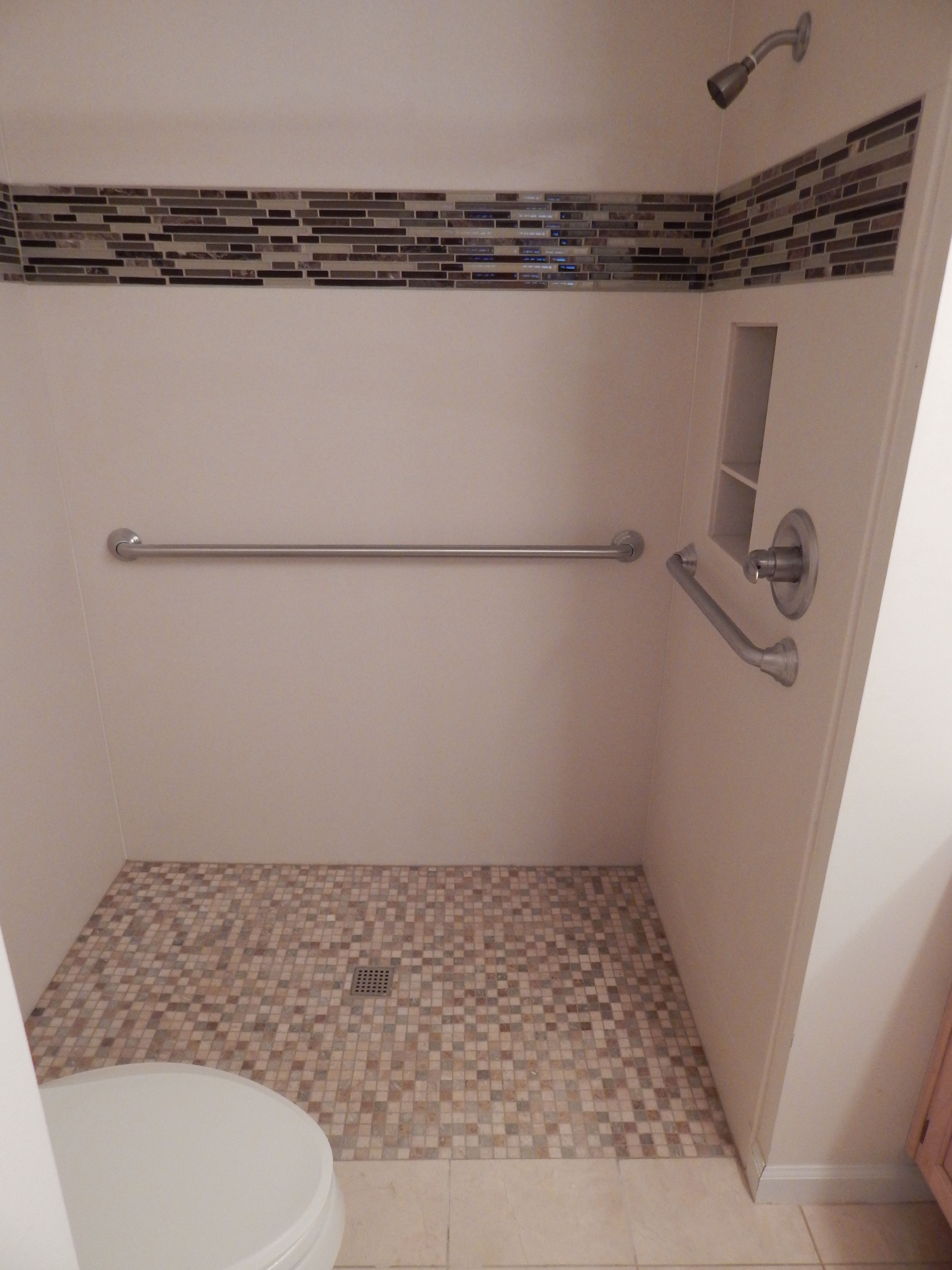 This zero barrier custom shower features a corian wall surround this zero barrier custom shower features a corian wall surround with a tile inset we installed a recessed wall box and x slip resistant floor tile for a dailygadgetfo Images