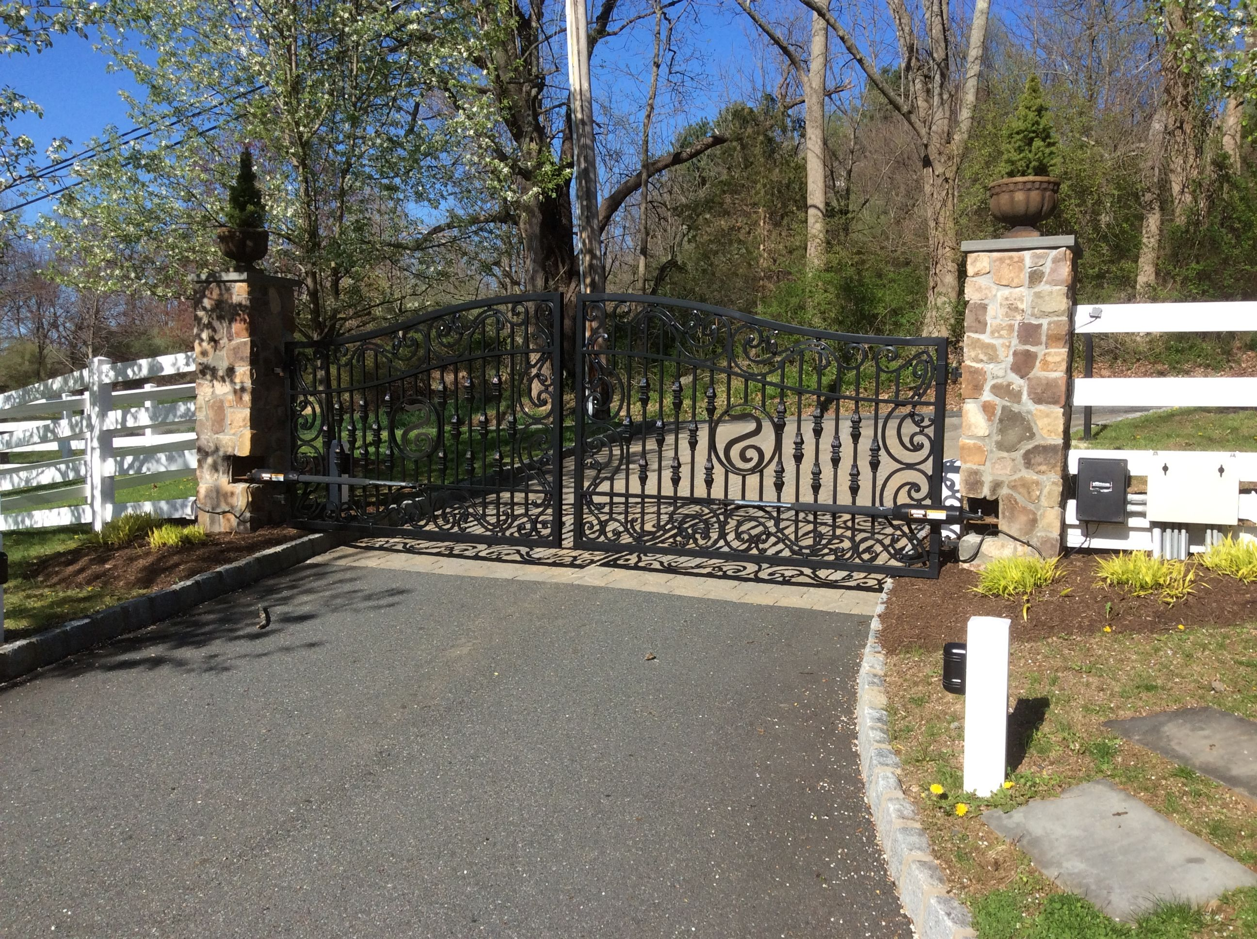 Sophisticated iron driveway gates with stone pillars