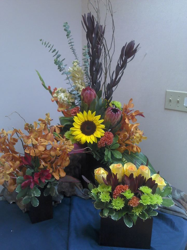 a trio of tropical arrangements to compliment each other in dark bamboo cubes and rectangles filled with mokara orchids, safari sunset, pink ice protea, sunflowers, peach coxcomb, yellow roses and green poms