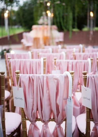 So thoughtful for a rainy day - beautiful chair treatments from @Marianne Symons Rentals for Special Events with umbrellas in design by The Wedding Belle. Photo by Beautiful Day Images. #wedding #chairtreatment #umbrella #pink