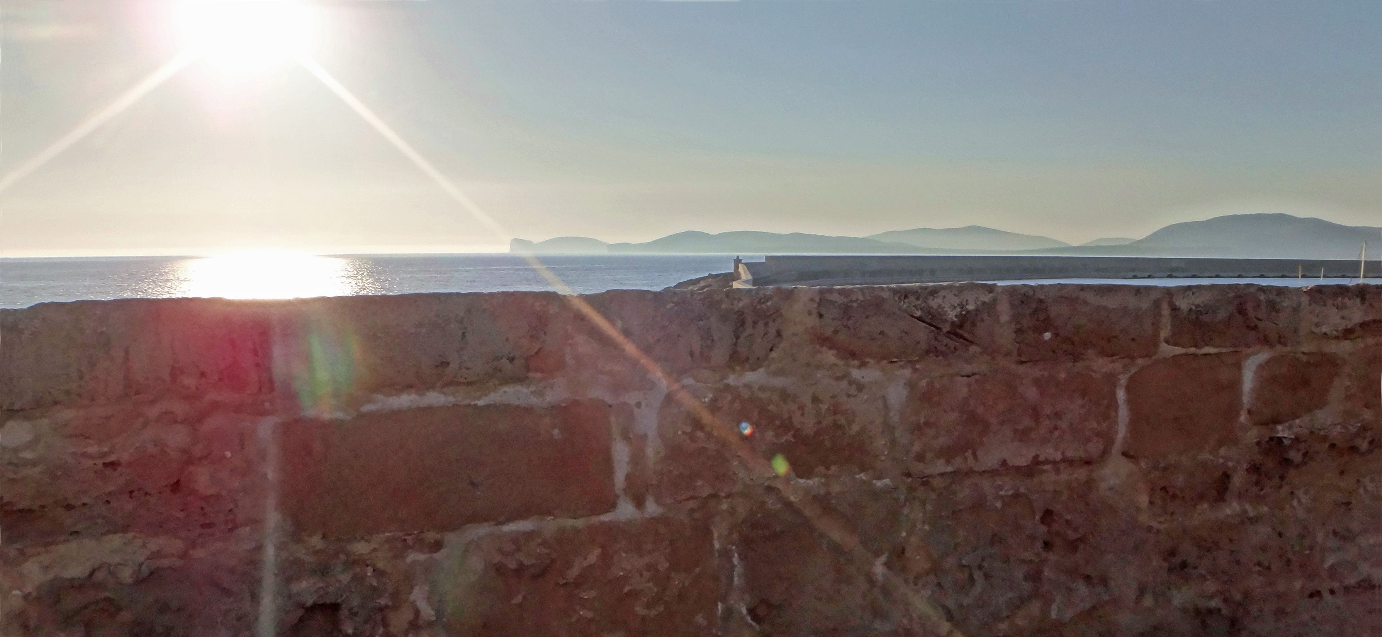 The sun climbs over the Alghero 's Bastions (built in 12th century by Doria) - Capo Caccia stands far, behind the pier. This is Sardinia.