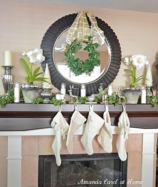 Carolers Displayed On A Mantle With Garland And Stockings: Christmas / Holiday Mantel. Greenery And White