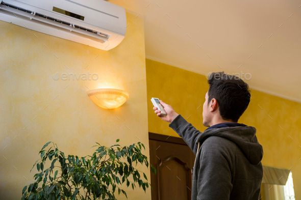 Young Man Switching On Or Adjusting The Wall Mounted Air - Living room air conditioner