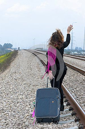Young woman with a suitcase at the railroad. Bidding farewell