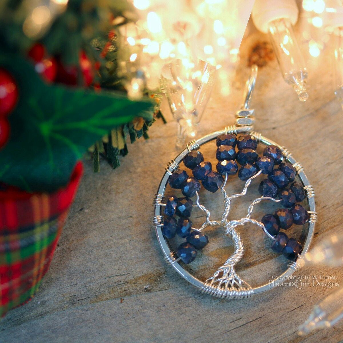 Recycled, eco-friendly Argentium sterling silver wire wrapped tree of life pendant with deep blue sapphire gemstones. Make her holiday shine with handmade jewelry from PhoenixFire Designs. Celebrating 10 years of luxury, quality, and beauty on etsy. 💜
