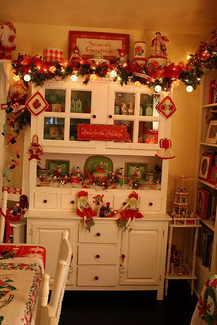 white hutch decorated for Christmas; red and white vintage Kitchen