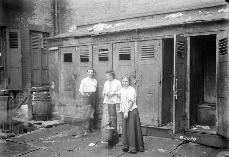 Two women & man in front of outhouses; one woman getting water. New ...