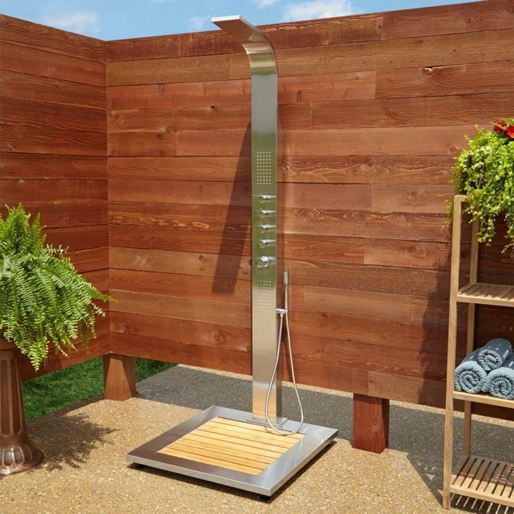 Die moderne Gartendusche wird von einem Sichtschutz aus Holz umgeben