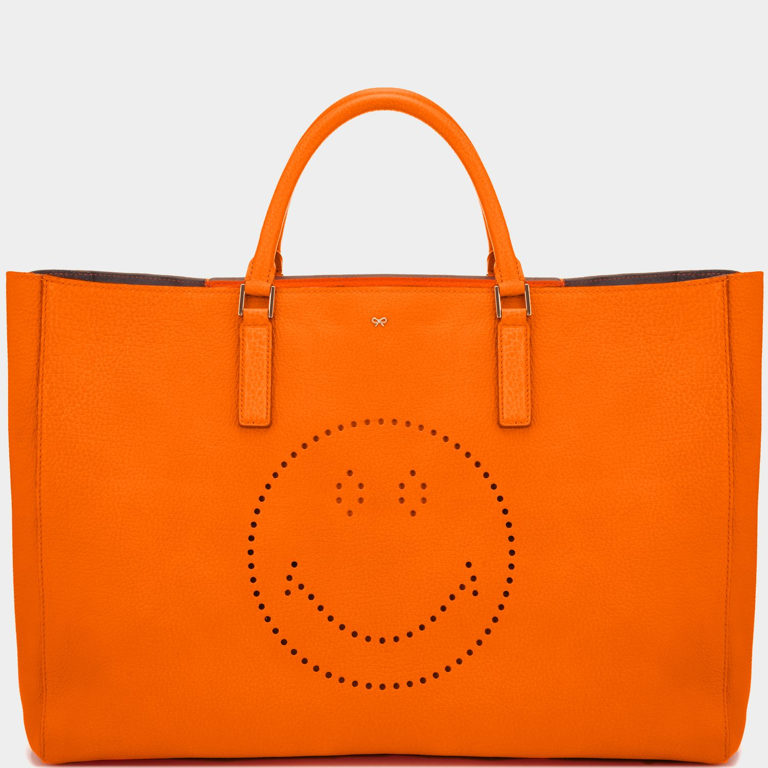 """<p style=""""margin-bottom:10px"""">To create the lightweight ,streamlined finish on the Featherweight Ebury we 've worked closely with our craftsmen to develop the technique used to fuse leather with a soft suede backing ,removing the need for any heavy additional stitching. This vibrant neon orange leather tote is finished with a whimsical punched out smiley face ,embodying our belief that fashion should always make you smile. Designed as a lightweight shell ,layer the ..."""