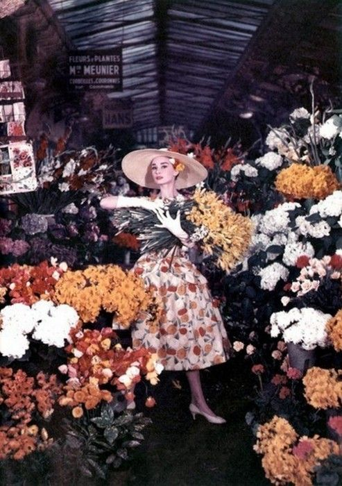 Audrey Hepburn in floral dress surrounded by flowers...