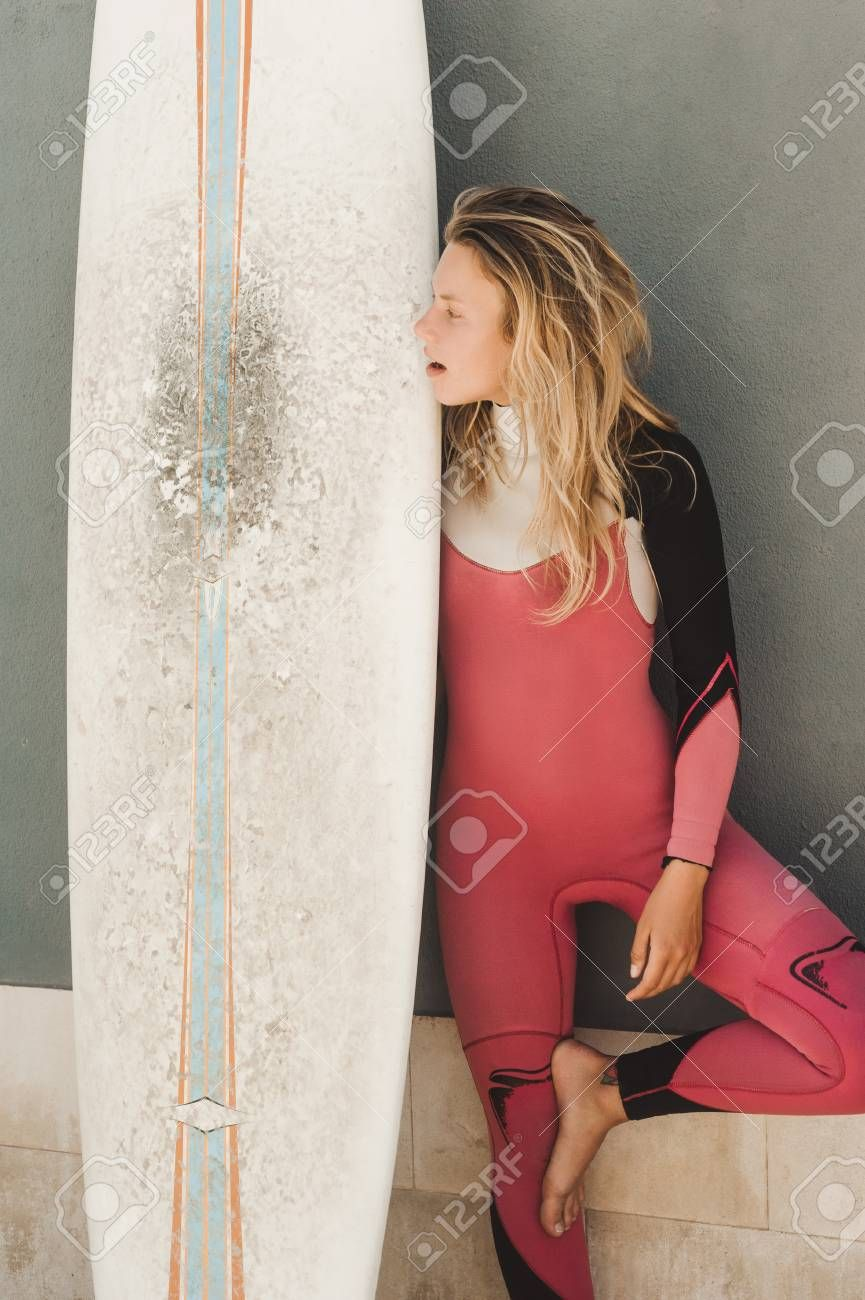 young woman in wetsuit with surfing board standing against grey wall Stock Photo ,