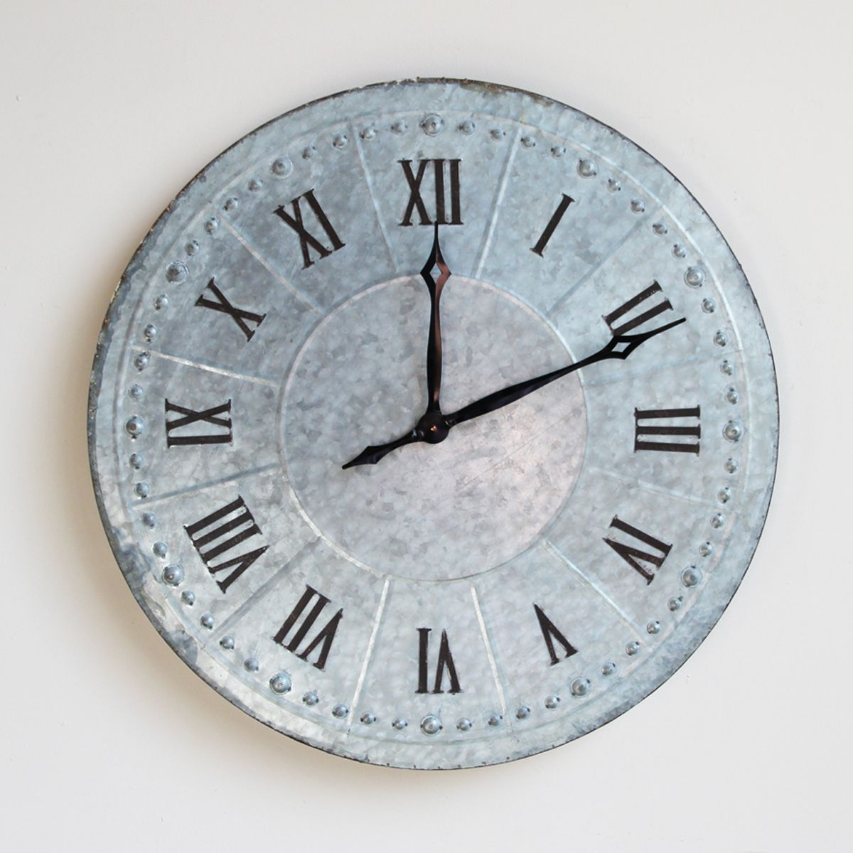 Oversized galvanized metal wall clock with roman numerals.  Battery operated.