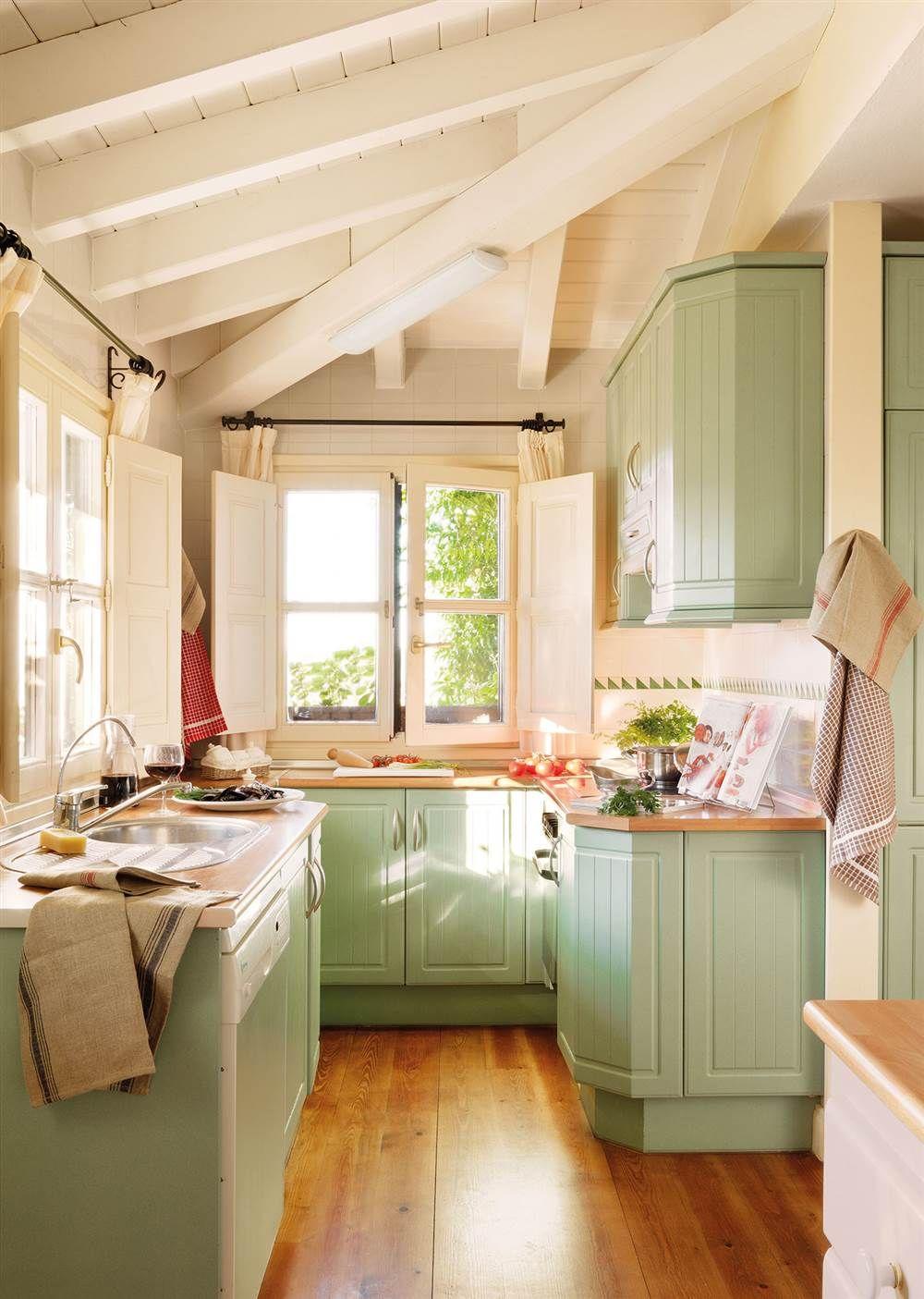 cocina campestre con vigas de madera y muebles en verde claro
