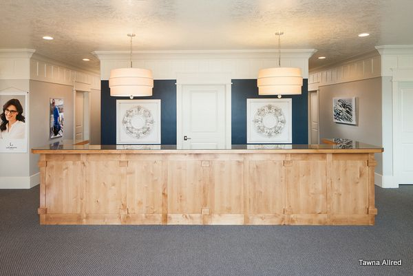 front desk, optometry office. large pendants, blue accent wall is