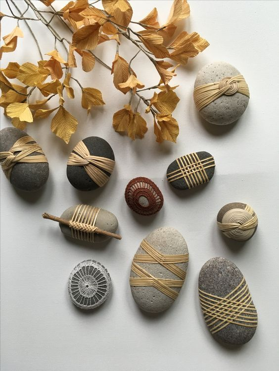 Photo of Stones wrapped in natural string with decorative patterns