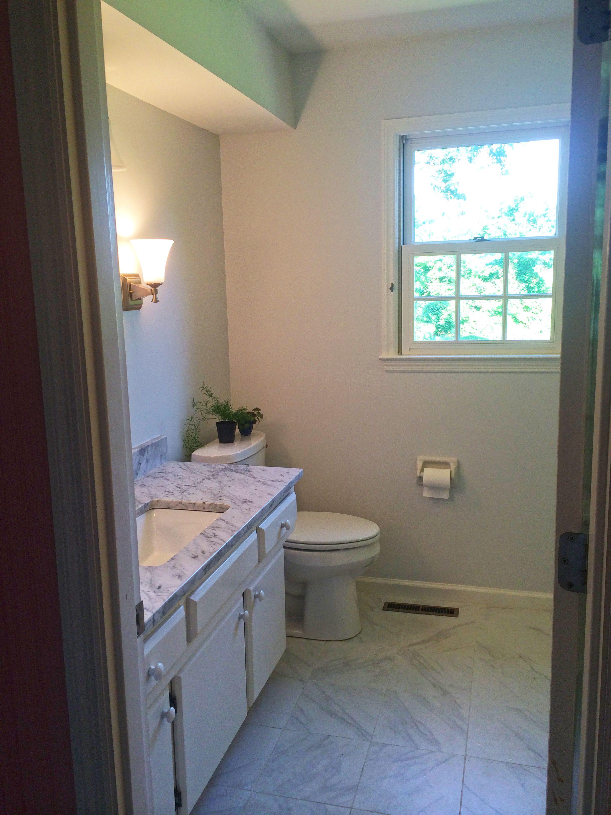 Bathroom Renovation - Daltile Carrara ceramic floor tile, White Carrara Granite countertop, undermount sink, Delta Faucet & Progress sconces and overhead lighting