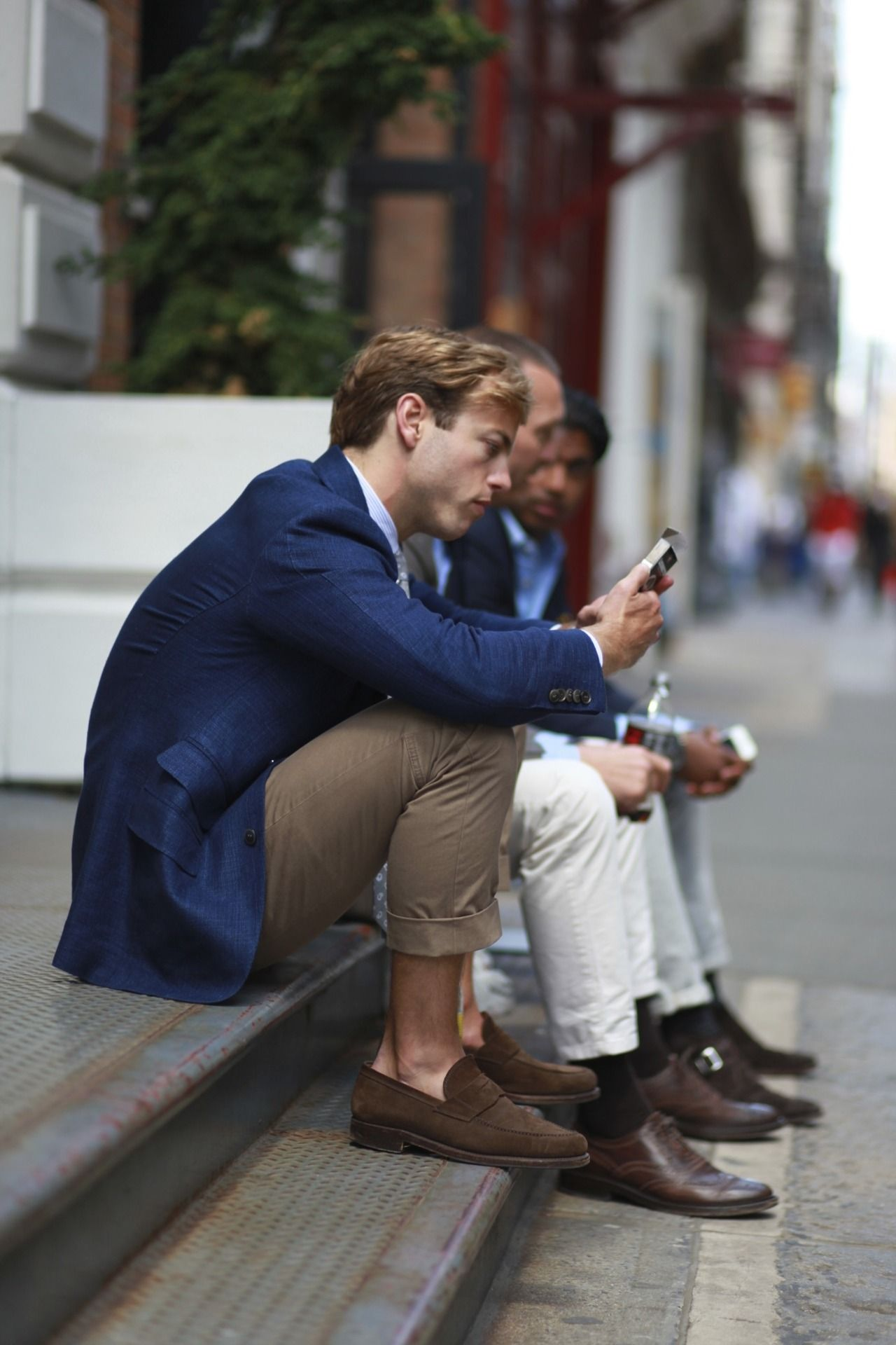 Guys on a stoop texting. Boy is wearing suede loafers with no socks, rolled up chinos, a blue blazer and blonde hair.