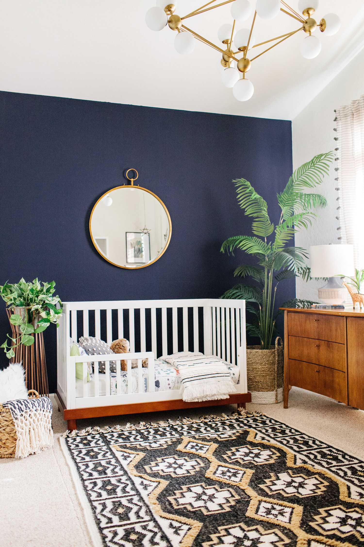 white modern toddler crib with boho rug, plants and gold hoop mirror.