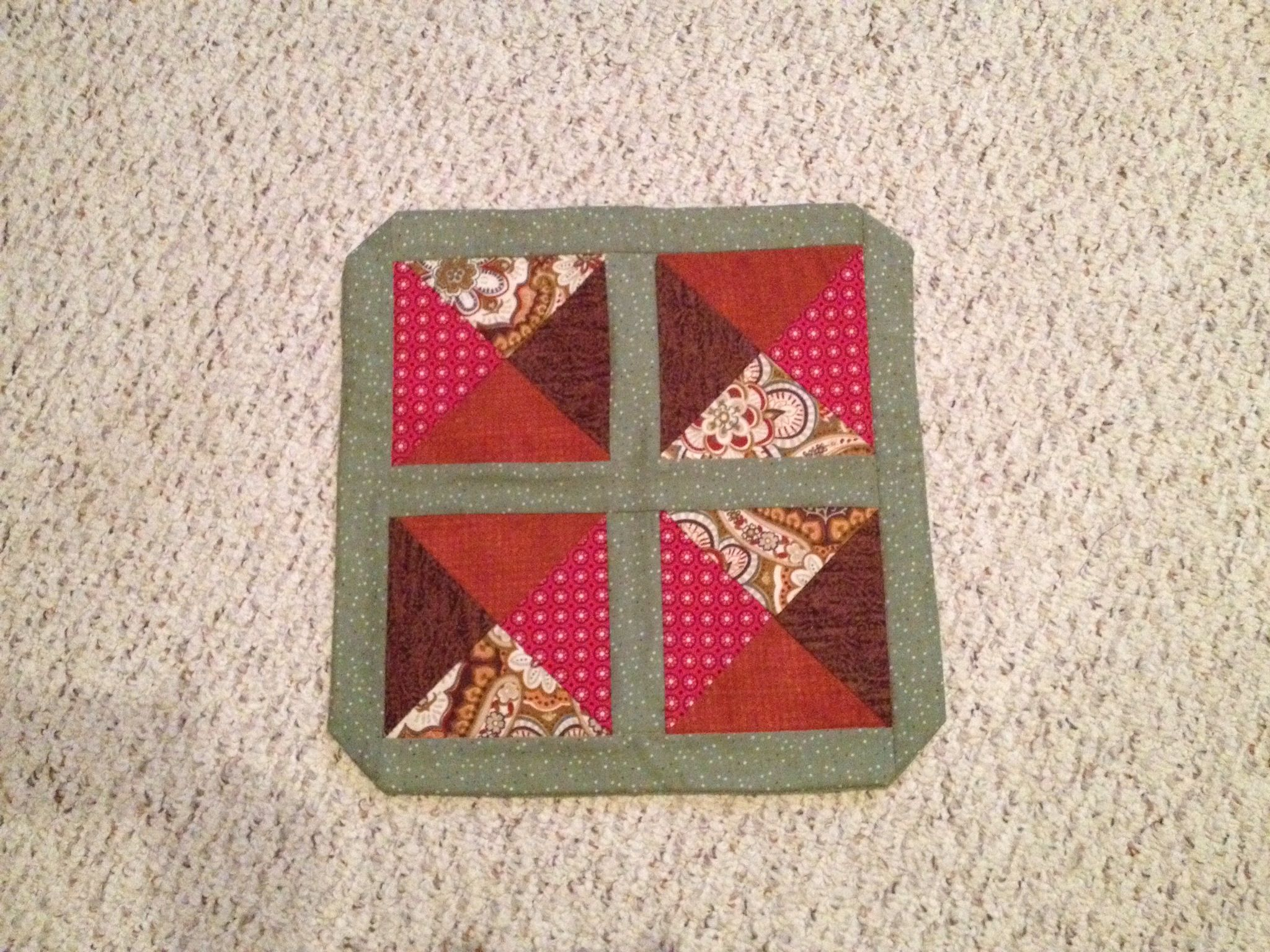 Square table centerpiece made from small quilt blocks.