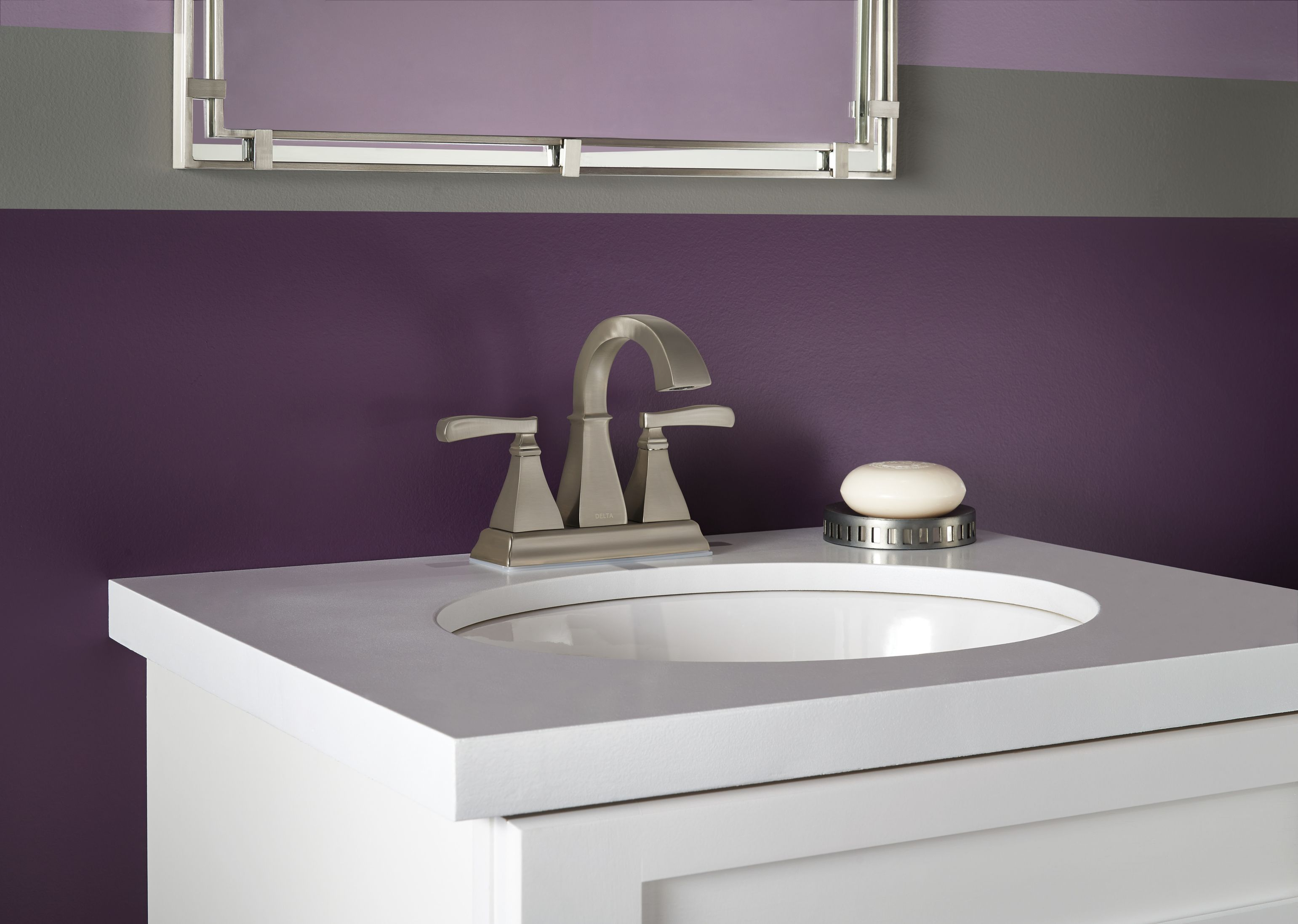 White Single Bathroom Sink With Purple Painted Walls And Brushed Nickel Faucet From The Delta