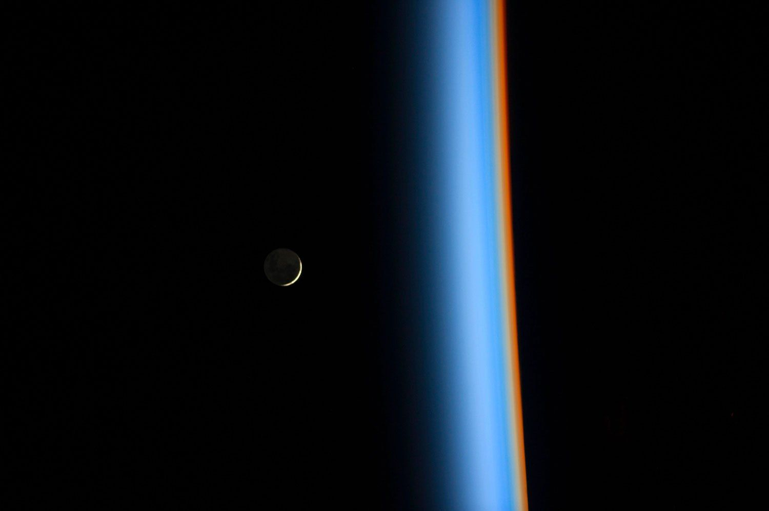 A crescent moon rises over the cusp of the Earth's atmosphere in this picture by Japan Aerospace Exploration Agency astronaut Koichi Wa...