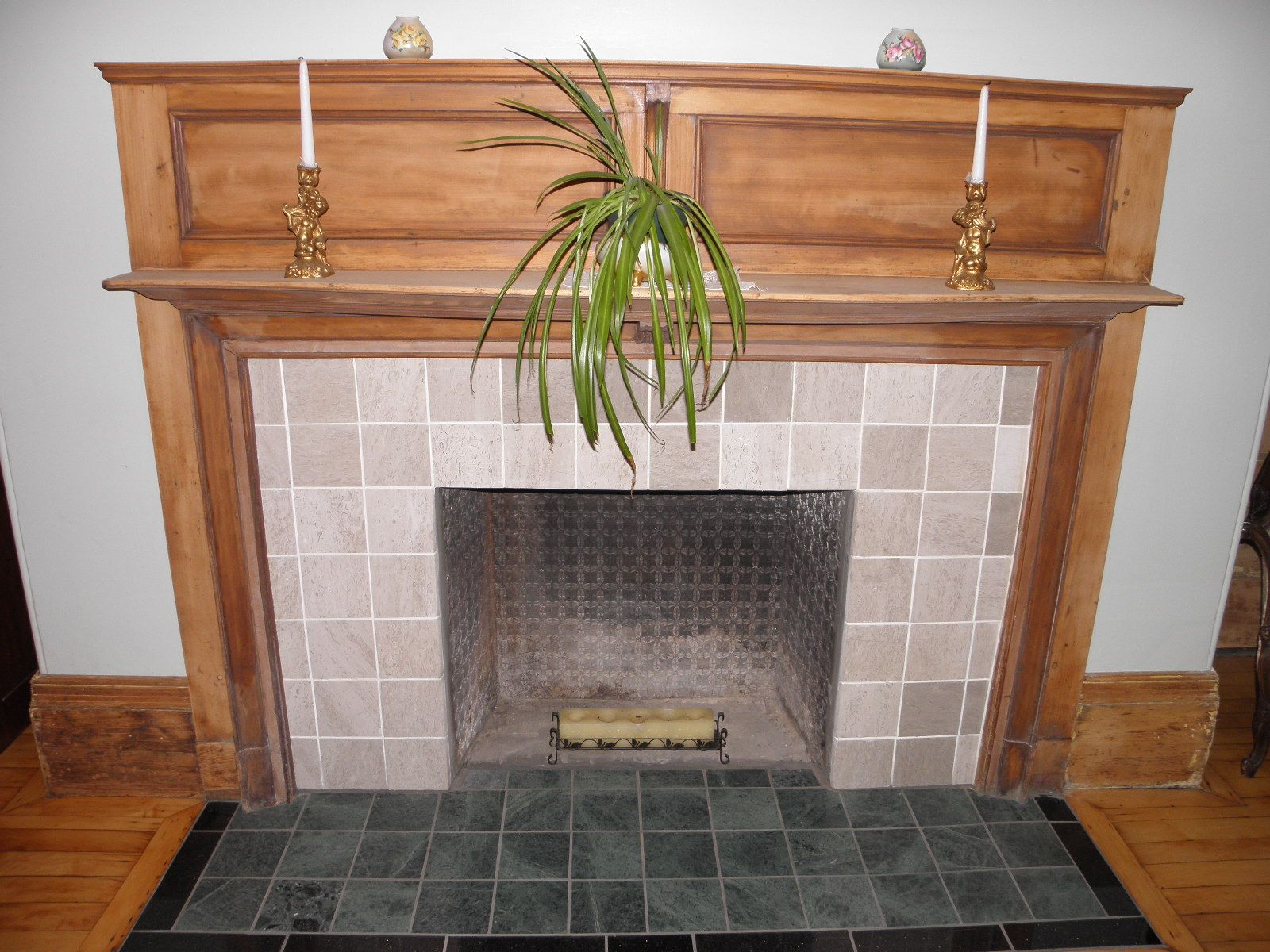 restored cherry wood fireplace mantle with a gray marble surround