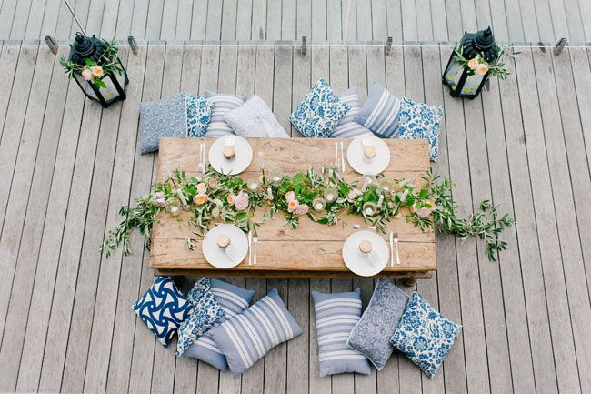 Oversize lanterns and an olive branch garland give a laid-back, Moroccan feel to…