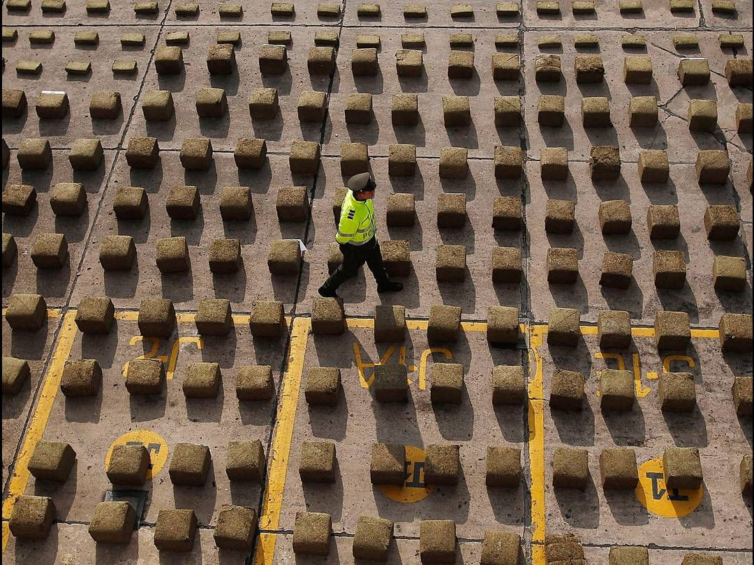 A police officer walks between packages of confiscated marijuana in the parking lot at the metropolitan police headquarters in Bogota. Three tons of marijuana were discovered hidden in a truck, making the pot bust one of the biggest seizures of the drug in a decade.