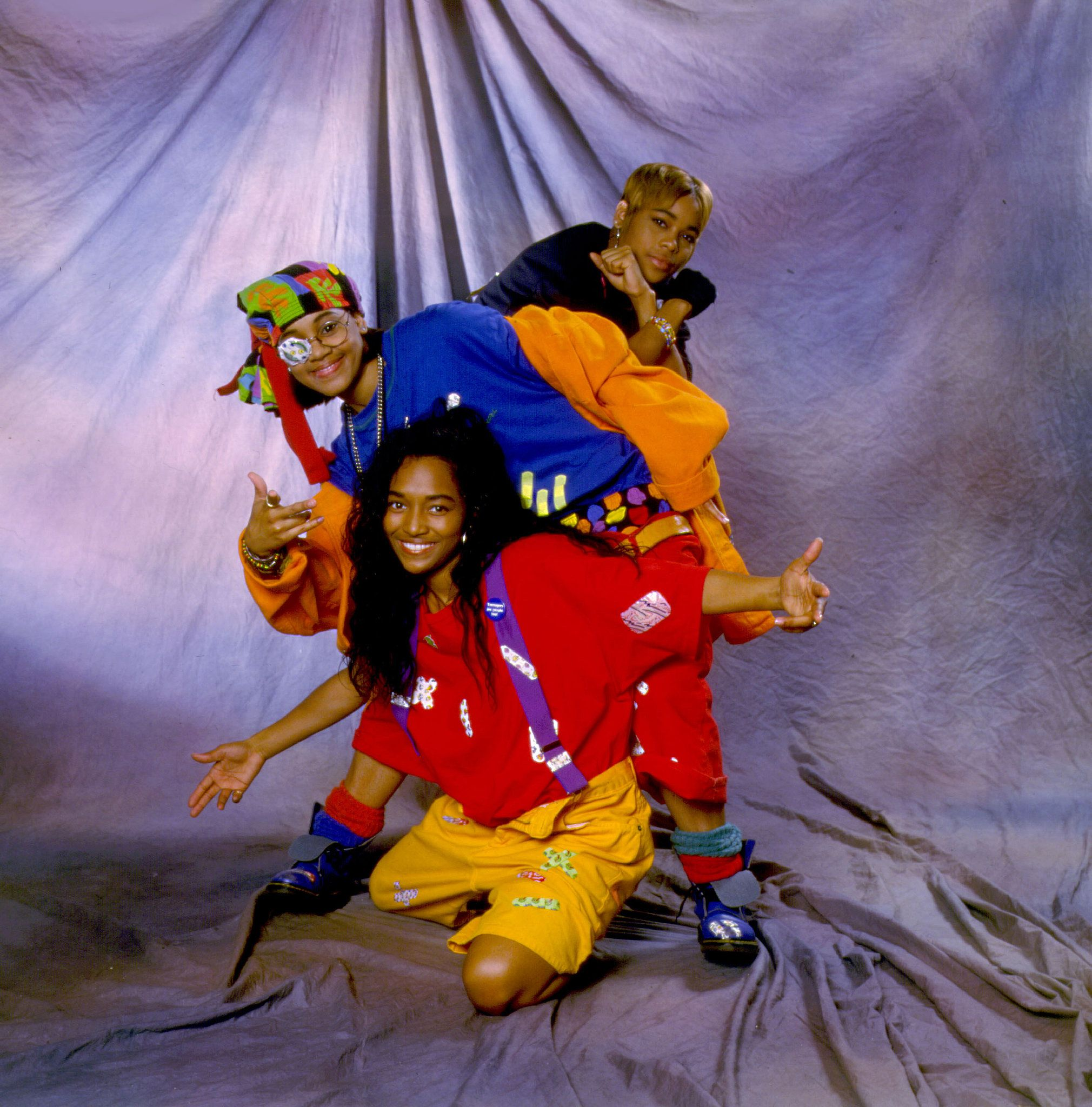 "To pull off Tionne ""T-Boz"" Watkins, Lisa ""Left Eye"" Lopes, and Rozonda ""Chilli"" Thomas of the R&B group TLC, you'll need bright, baggy clothes, caps turned backward, suspenders, and either a patch or a black mark under the eye of whoever's Left Eye. Going around singing ""Waterfalls"" is optional but advised."