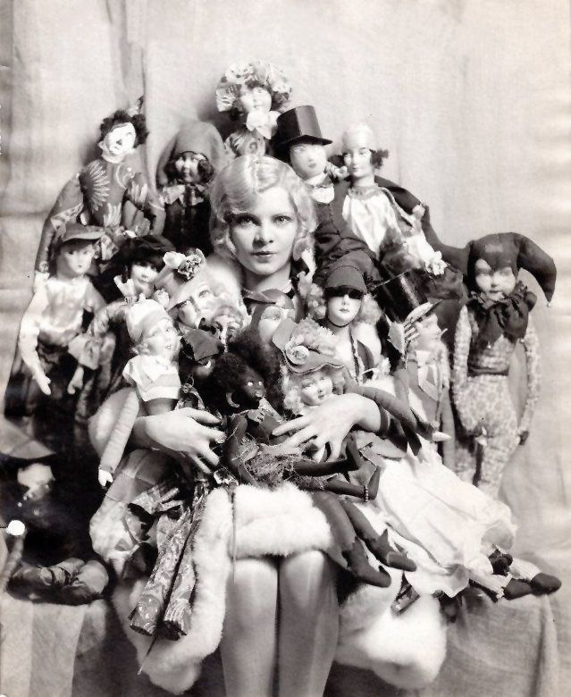 American actress Claire Luce with a gaggle of boudoir dolls