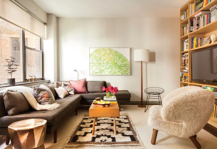 Small modern New York City studio with dunbar sofa, Finn Juhl pelican chair, wire, chair, and BDDW coffee table in the living area