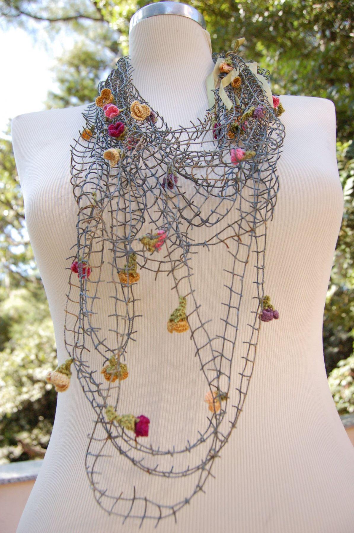 Colar feito com rede de pesca reciclada em tonalidade azul desbotado (naturalmente pelas intempéries),  contendo em média treze florinhas feitas em crochet manual por mulheres da Comunidade de Governado...