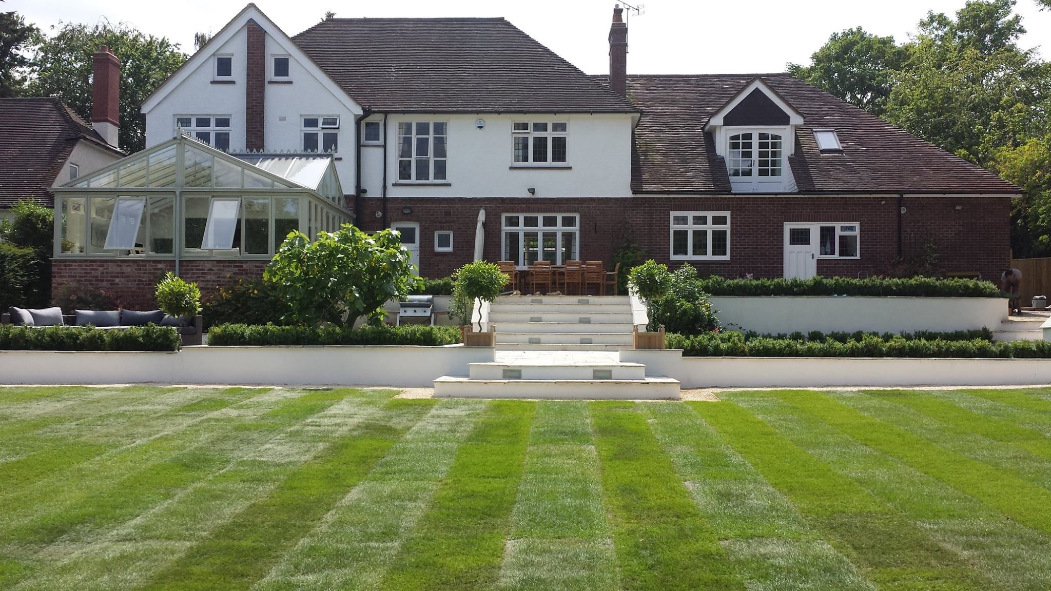 Large family garden, new lawn, block rendered walls, steps, lighting, lots of box hedging and cotswold gravel paths