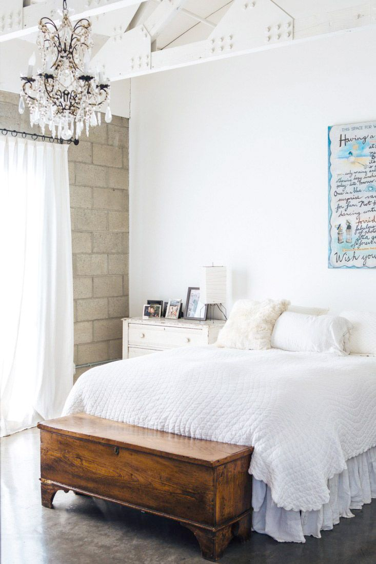 White bedroom with small chandelier and brick walls