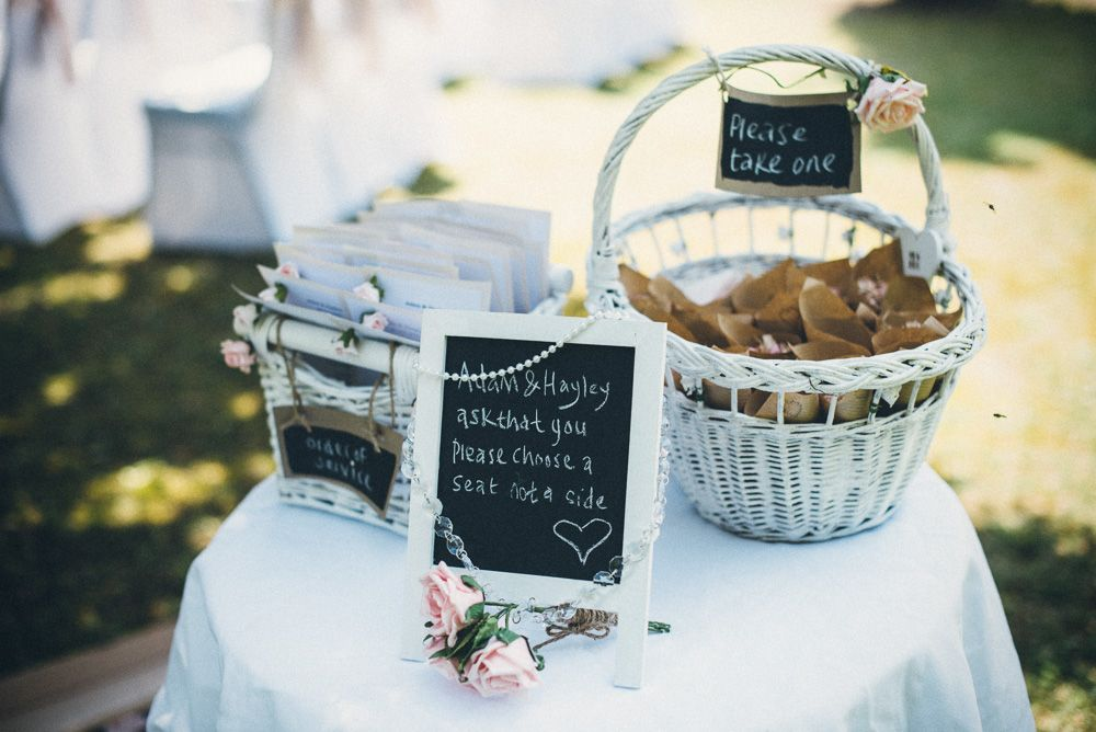 Flowers and white wicker baskets holding orders of service and confetti! © Susie Lawrence Photography #luxuryweddingsfrance #frenchweddings #rusticweddings #rustic #weddingideas #weddingsabroad #bellevue #southwestfranceweddings #love #marriage #weddings #countrysidewedding #summerwedding #susielawrence #confetti #wickerbasket #blackboard #julywedding