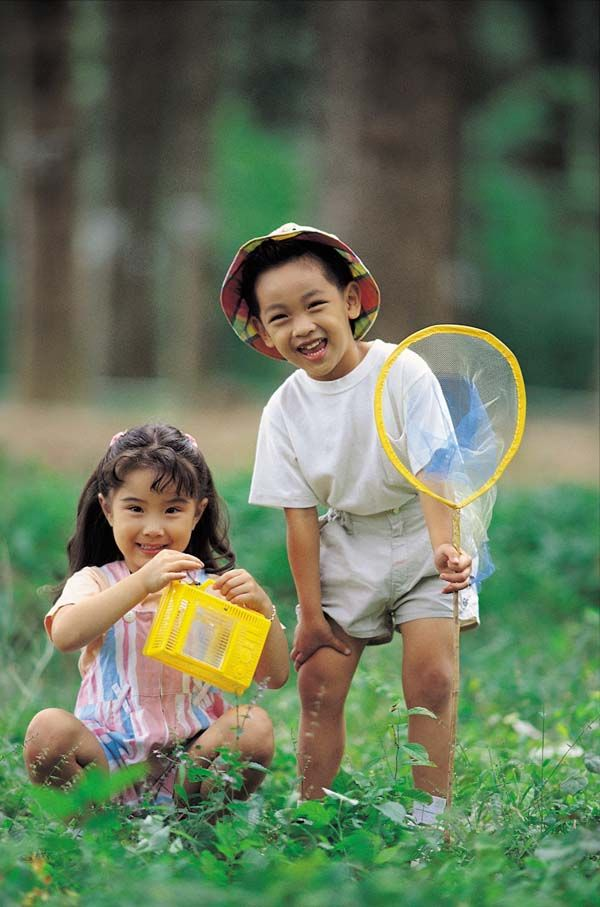 c665c20f77 A photo of two young Asian children standing grinning in a field – a girl  and