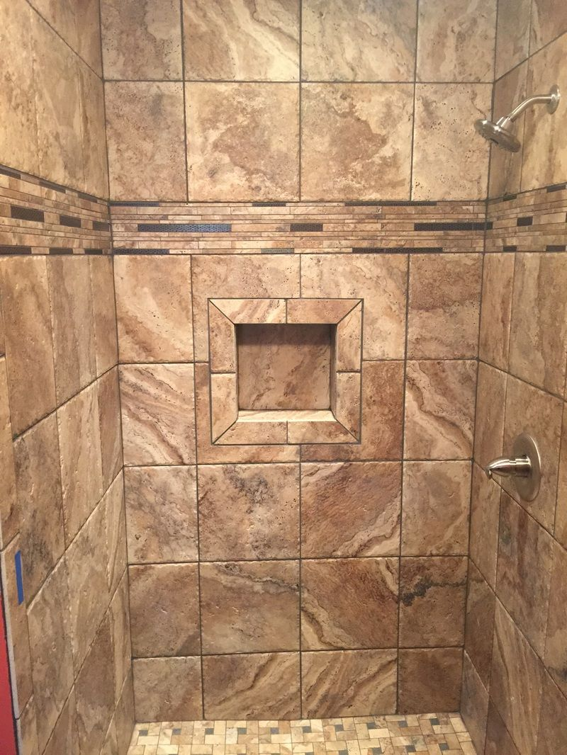 Warm brown porcelain tiled shower with niche, stone accent stripe ...