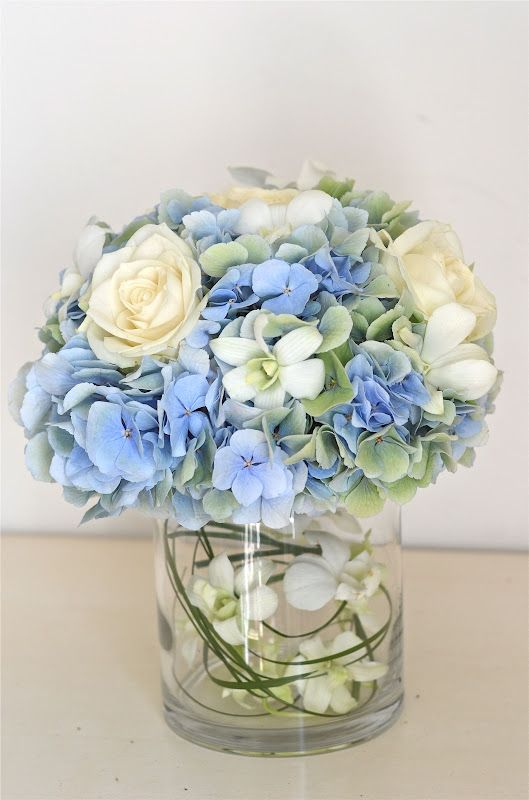 Hydrangea Centerpiece As One Of The Three Vases On The Tables I Like How The Other Flowe Blue Hydrangea Centerpieces Flower Centerpieces Ivory Wedding Flowers
