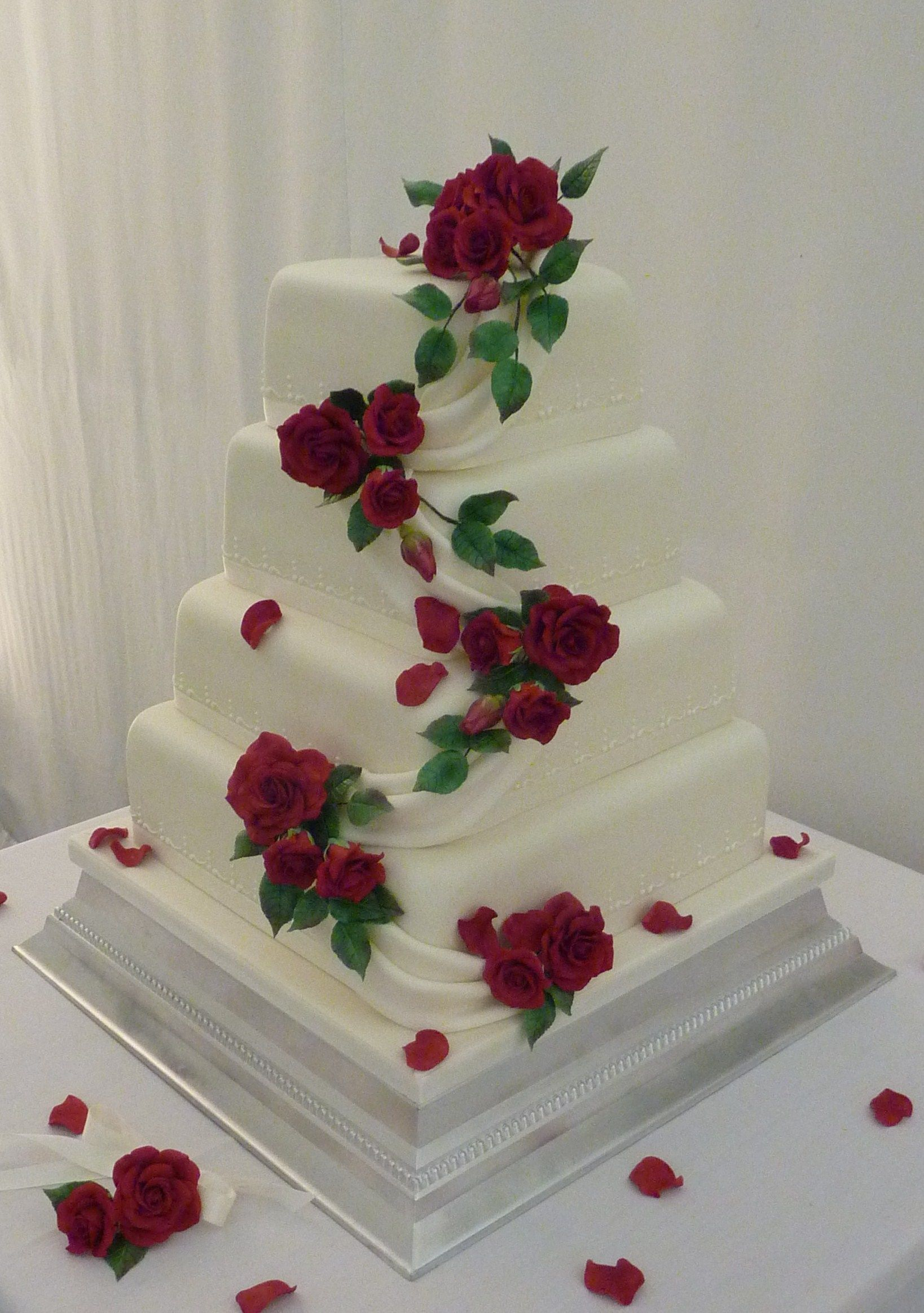 Offset square wedding cake with red sugar roses and petals cakes