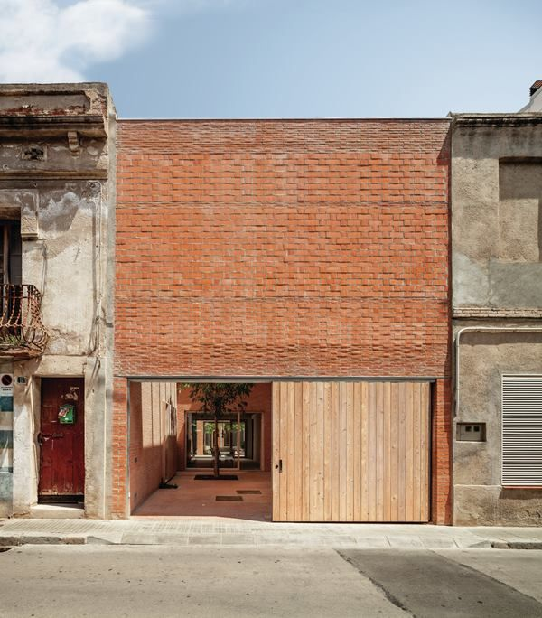 A new masonry wall forms the rear façade, along a street that is open to vehicular traffic. Wood sliding doors reveal  a terrace that doubles as a garage. As with the front terrace, a retractable glazed roof facilitates year-round use.