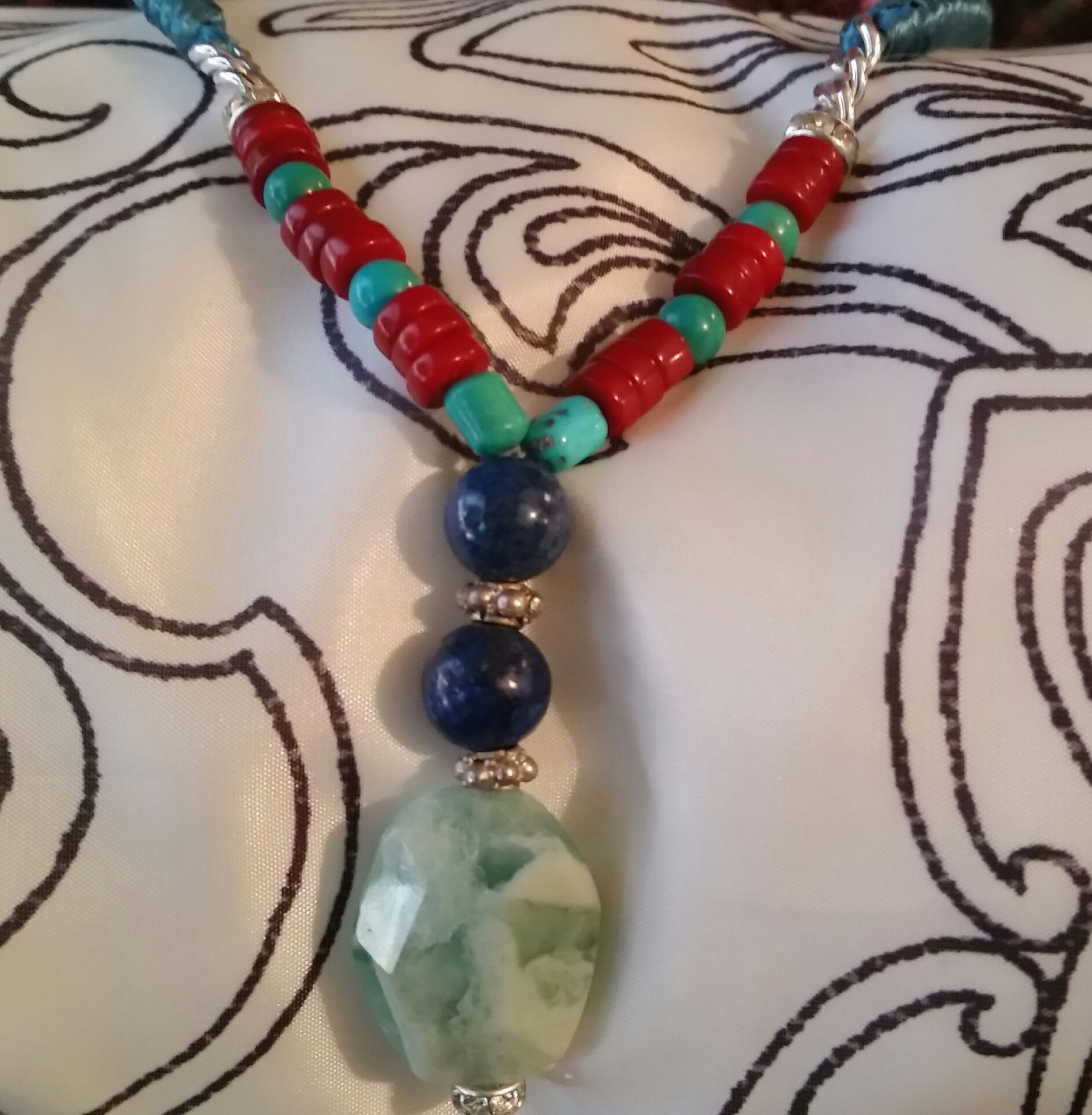 This necklace was created with ocean blue silky rope, natural coral, natural turquoise, lapis lazuli/bali silver spacers and an amazonite natural stone,
